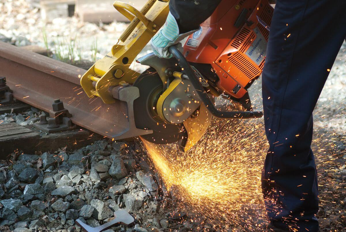 photo of a person cutting railroad tracks many sparks are flying