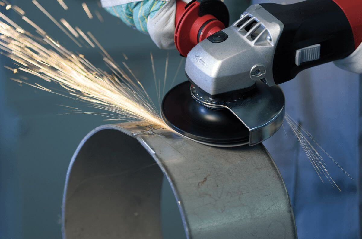 photo with a person using an angle grinder with fiberdisc on an iron tube, sparks fly