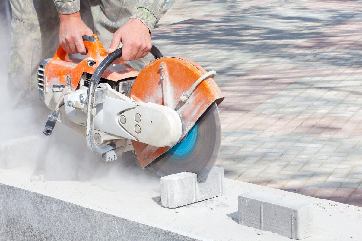 photo of a road construction scene: man holding running power cutter with stone cutting disc