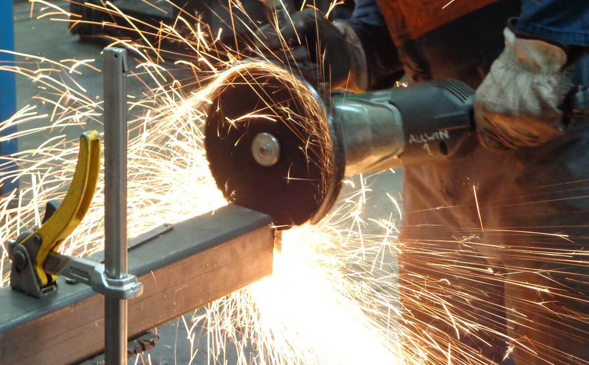 photo of a person holding a running industrial angle grinder cutting an iron tube, many sparks flying
