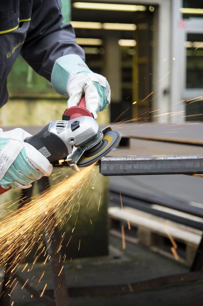 photo of a person wearing gloves and angle grinder for edge grinding, sparks flying